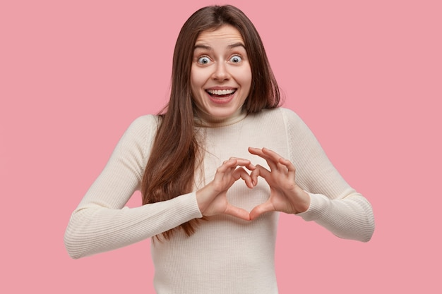 Love and care concept. beautiful woman smiles broadly, shows heart sign over chest, wears casual clothes, has happy exxpression, stands against pink background