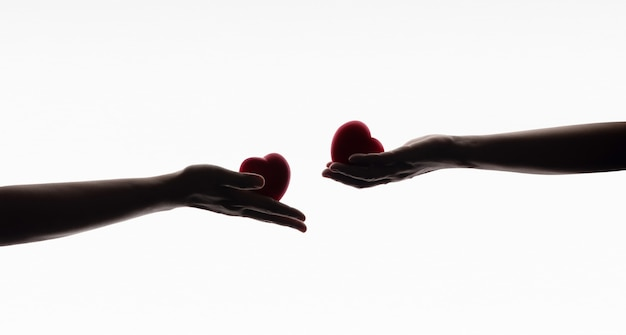 Love, care, donation and sharing concept. silhouette of hands with heart symbol