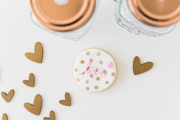 Love circular cookie with heart shapes and jar on white backdrop