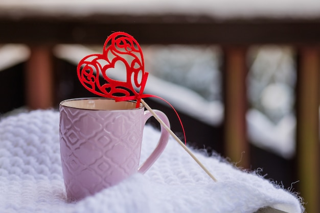 Love at coffe time, christmas concept, mug and red heart decoration on a snow balcony.