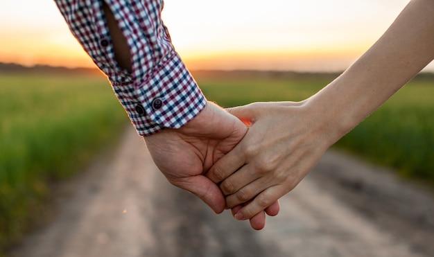 愛の概念。日没時に手をつないでいるカップル、愛と幸せな関係の象徴。恋をしている若いカップルが日没時に畑を歩き、手をつないで夕日を眺める