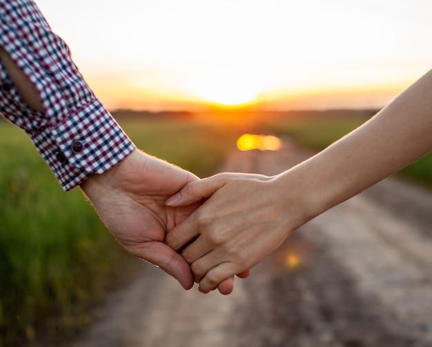 愛の概念。日没時に手をつないでいるカップル、愛と幸せな関係の象徴。恋をしている若いカップルが日没時に畑を歩き、手をつないで夕日を見ている