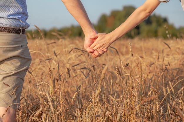 사랑 개념입니다. 일몰 동안 손을 잡고 있는 커플, 사랑과 행복한 관계의 상징. 사랑에 빠진 젊은 부부는 석양에 밀밭을 걷고 손을 잡고 석양을 바라보고 있다