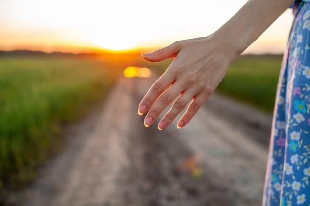 Концепция любви. женская рука в поле на дороге на фоне заката. молодая влюбленная пара гуляет по полю на закате, держась за руки и глядя на закат