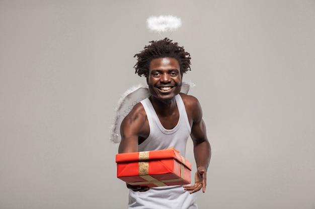 사랑 개념 및 공유 goft. 흰 셔츠, 후광, 윙크를 하고 선물 상자를 들고 있는 어두운 피부의 수염이 난 아프리카 천사 재미있는 남자. 그것은 당신을 위해. 실내, 회색 배경에 고립