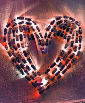 Концепция любви и день святого валентина. машины припаркованы в форме сердца на стоянке. с высоты птичьего полета.