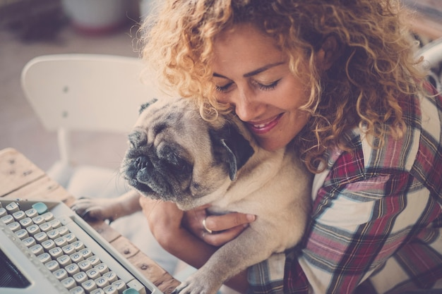Love concept for beautiful curly blonde middle age caucasian woman and her best friend old dog pug