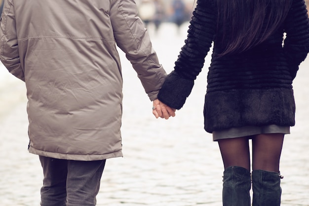 Love concept. couple holding hands each other while going for a walk in winter street, view from back