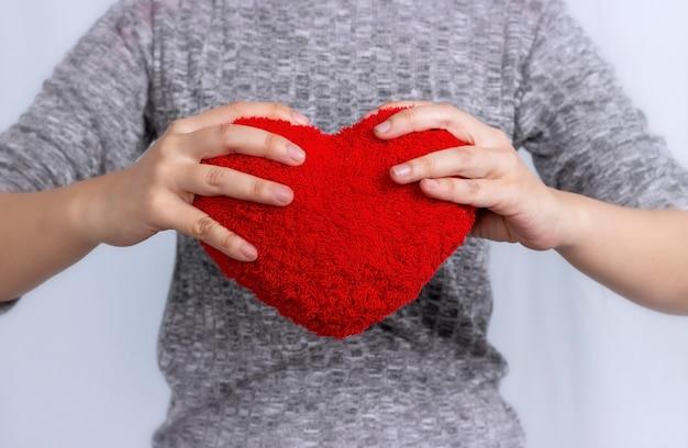 Любовь концепции руки, держа куклу с красным сердцем