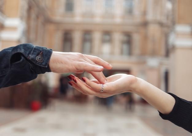 Концепция любви. руки влюбленной пары на фоне городской архитектуры