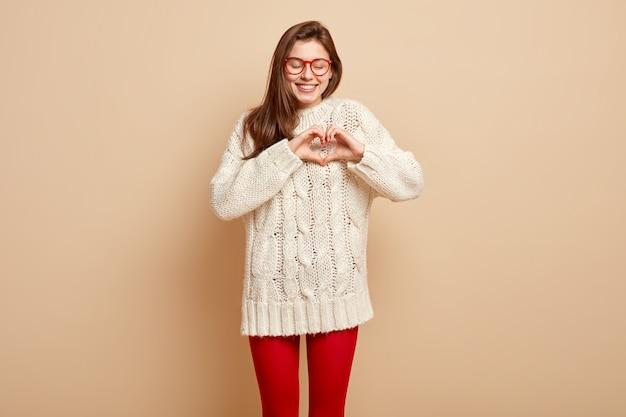 愛の概念。幸せな笑顔のガールフレンドは、ベージュの壁に隔離された白いジャンパーを着て、指で心のジェスチャーをし、良い気持ちを表現します。手話の概念。慈善のシンボル