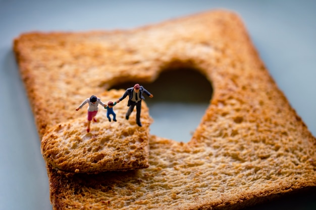 Love concept. miniature of happy family walking on burned sliced toasted bread with a shape of heart