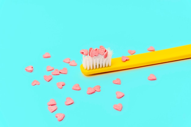 Love concept minimal. bright colorful background with teethbrush and candy hearts in pink and turquoise colors.
