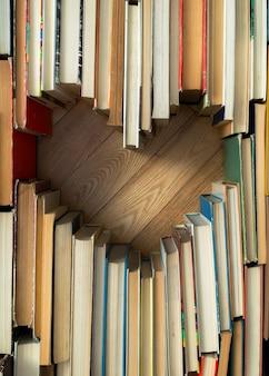 나무 바닥에 오래 된 빈티지 책에서 심장 모양의 개념을 사랑 해요.