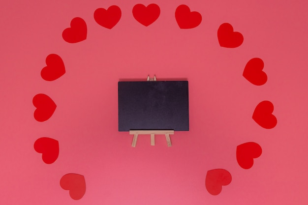Love concept. red small heart put around the blackboard those placed on a pink