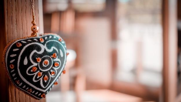 Концепция любви с декоративным висящим сердцем и несосредоточенным домом