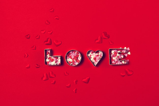 Love concept with letters love and hearts on a red background. t