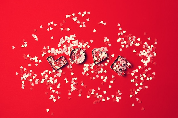 Love concept with letters love and sweethearts on a red backgrou
