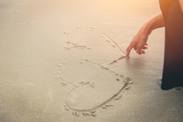 Love concept, women hand draw heart on the beach.