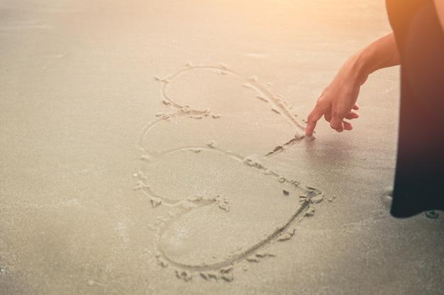 사랑 개념, 여자 손 해변에 마음을 그립니다.