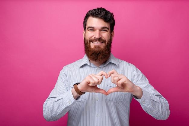 愛の概念。心臓のジェスチャーをしているカメラに微笑んでいる若いひげを生やした男。