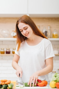 요리를 좋아합니다. 건강한 식습관. 레저 및 라이프 스타일. 샐러드 야채를 자르고 젊은 여자를 웃고.