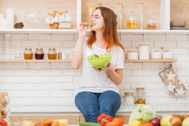 요리를 좋아합니다. 취미와 생활 방식. 부엌 카운터에 앉아서 그린 샐러드를 먹는 귀여운 젊은 여성.