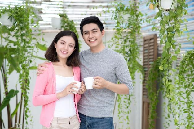 自宅でカップルが大好きです。バルコニーの庭でリラックスした若いアジア人。
