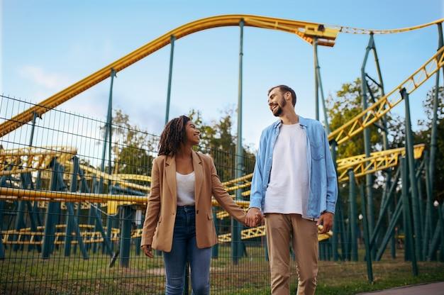 Влюбленная пара на американских горках в парке развлечений, аттракционе. мужчина и женщина отдыхают на открытом воздухе. семейный отдых летом, развлекательная тематика