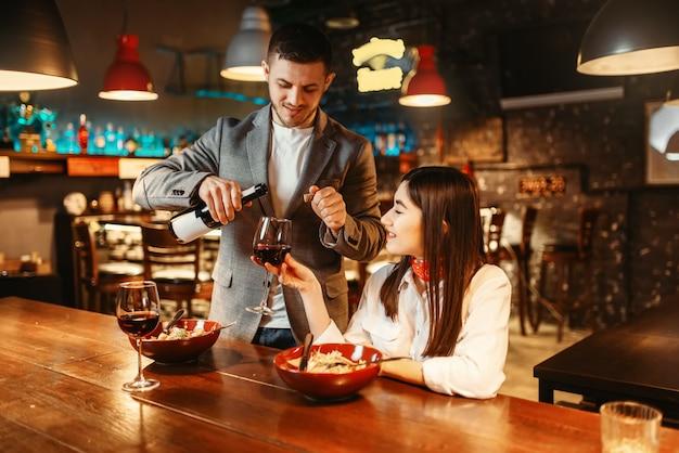 木製のバーのカウンター、ロマンチックなデートのお祝い、ペーストと赤ワインのディナーで愛のカップル。ナイトクラブで一緒にリラックスしたパブ、夫と妻の恋人レジャー