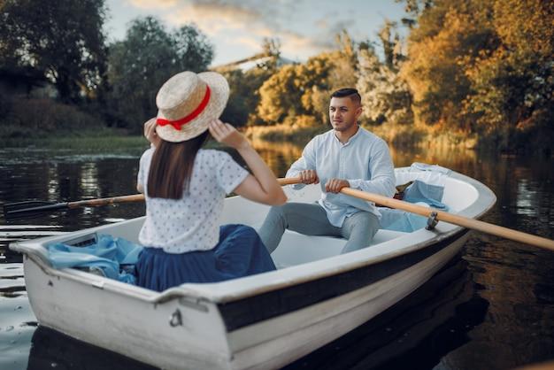 夏の日に湖でボートを愛するカップル