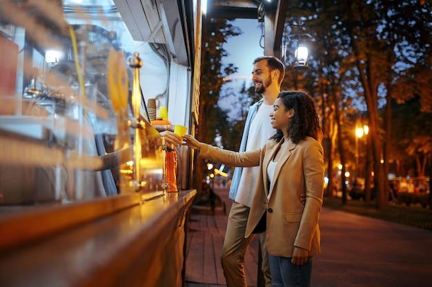Влюбленная пара, покупающая кофе в городском парке развлечений. мужчина и женщина отдыхают на открытом воздухе. семейный отдых летом, развлекательная тематика