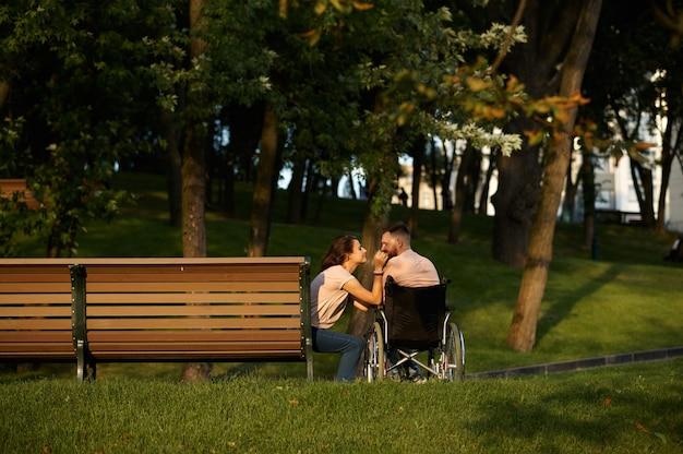 Влюбленная пара, уход за инвалидом в инвалидной коляске