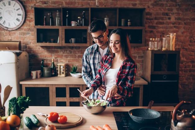 Влюбленная пара готовит на кухне, приготовление овощного салата. мужчина и женщина готовят романтический ужин
