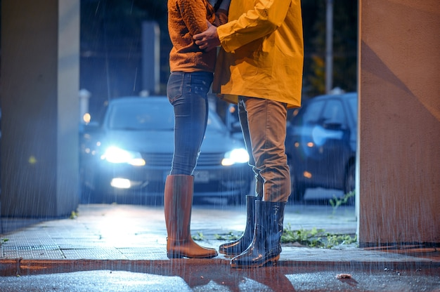 Love couple dating in night park, summer rainy day. man and woman in rain, romantic date on walking path, wet weather in alley