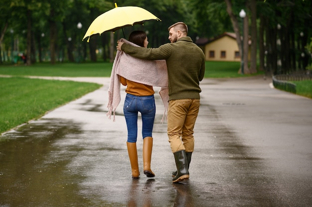Love couple drinks hot coffee in park, summer rainy day. man and woman stand under umbrella in rain, romantic date on walking path, wet weather in alley
