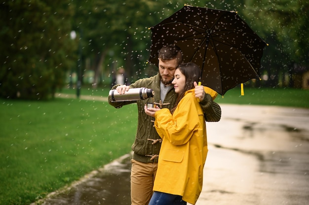 Love couple drinks hot tea in park, summer rainy day. man and woman stand under umbrella in rain, romantic date on walking path, wet weather in alley