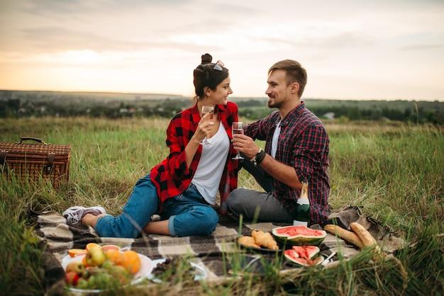 愛のカップルは、夏の畑でピクニックワインを飲みます。ロマンチックなジャンケット、男性と女性のレジャー、一緒に幸せな家族の週末