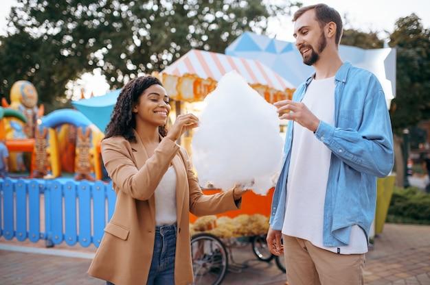 도시 놀이 공원에서 솜사탕을 먹는 사랑 커플. 남자와 여자는 야외에서 휴식을 취하십시오. 여름철 가족 레저, 엔터테인먼트 테마