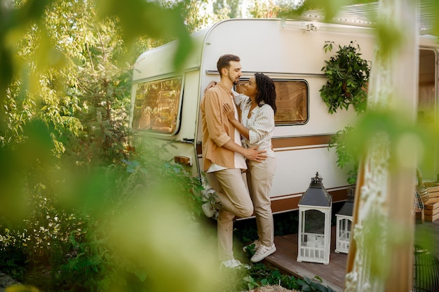 Love couple embraces in rv, camping in a trailer. man and woman travels on van, romantic vacations on motorhome, campers leisures in camping-car
