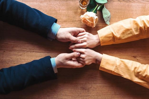 Влюбленная пара вручает на деревянных фоне. отношения мужчины и женщины