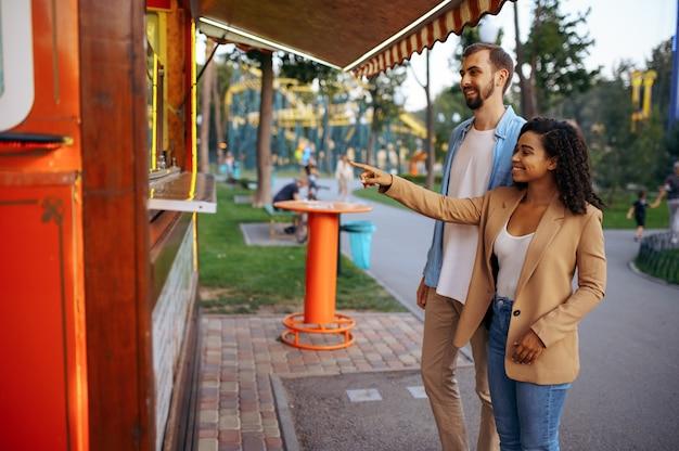 Влюбленная пара весело в парке развлечений, аттракционе американских горок. мужчина и женщина отдыхают на открытом воздухе. семейный отдых летом, развлекательная тематика