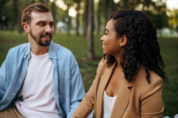 Влюбленная пара, взявшись за руки, гуляя в парке. мужчина и женщина сидят на траве. семейный отдых на лугу летом, выходные на природе