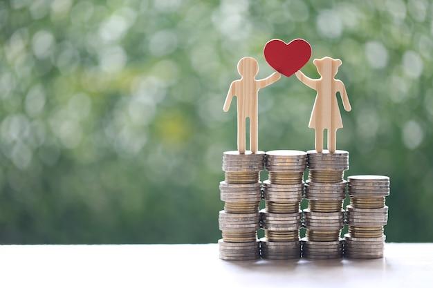 自然な緑の背景にコインのお金のスタックに立っているハートの形を保持している愛のカップル