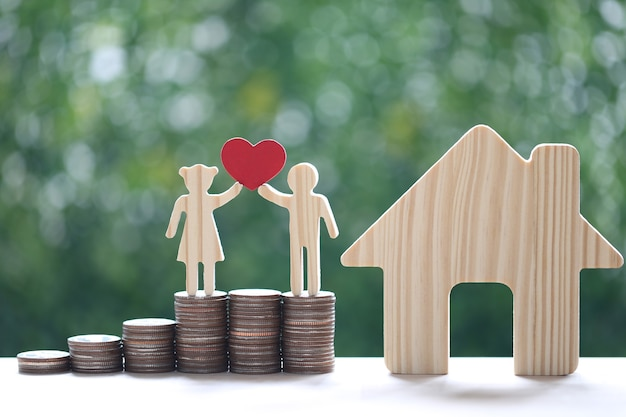 Love couple holding heart shape standing on stack of coins money with model house on natural green background, saving for lover or family and save money for prepare in future concept