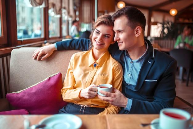 カップルの抱擁を愛し、レストランの窓を見てください。男と女の美しい関係