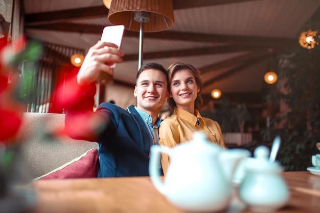 愛するカップルが抱擁し、電話のカメラで自分撮りを作る