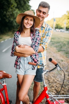 Love couple hugs in summer park,vintage bike, romantic date of young man and woman.
