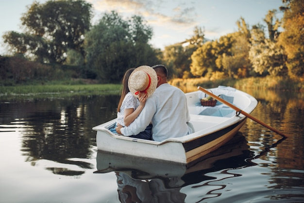 Love couple kissing in boat on lake