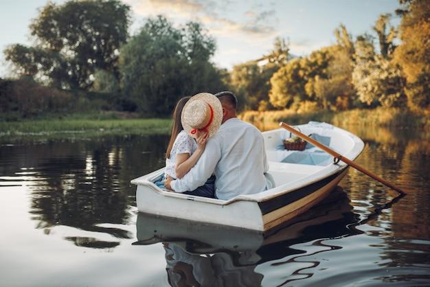 Влюбленная пара, целующаяся в лодке на озере